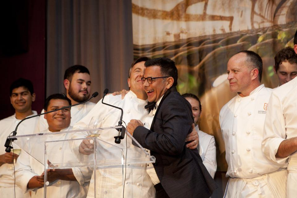 Chef Daniel Boulud and Daniel Johnnes hugging after a successful event in New York City