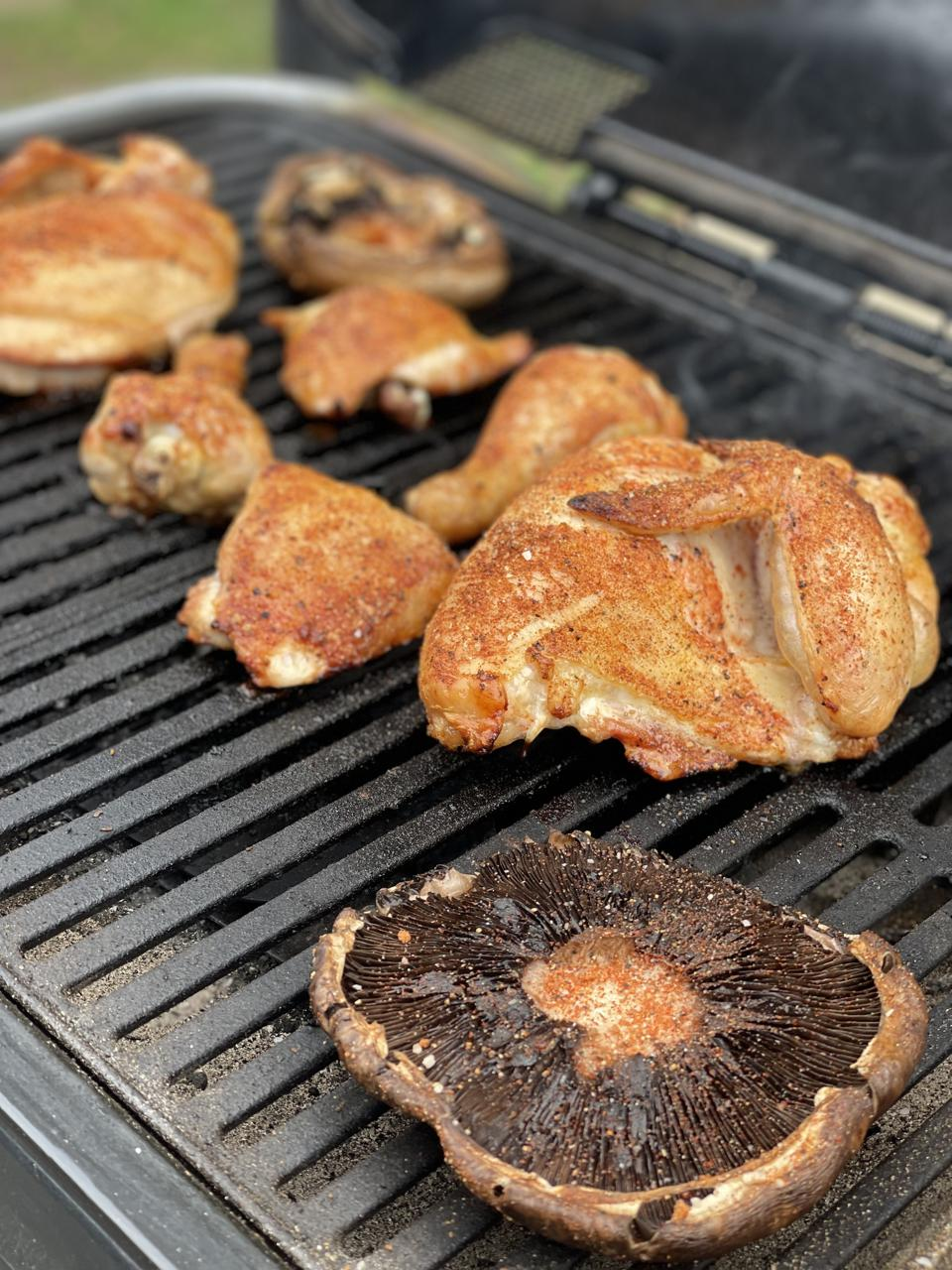 Spice Rubbed BBQ Chicken and Portobello mushrooms are photographed on the cooking grates of the Spark Grill