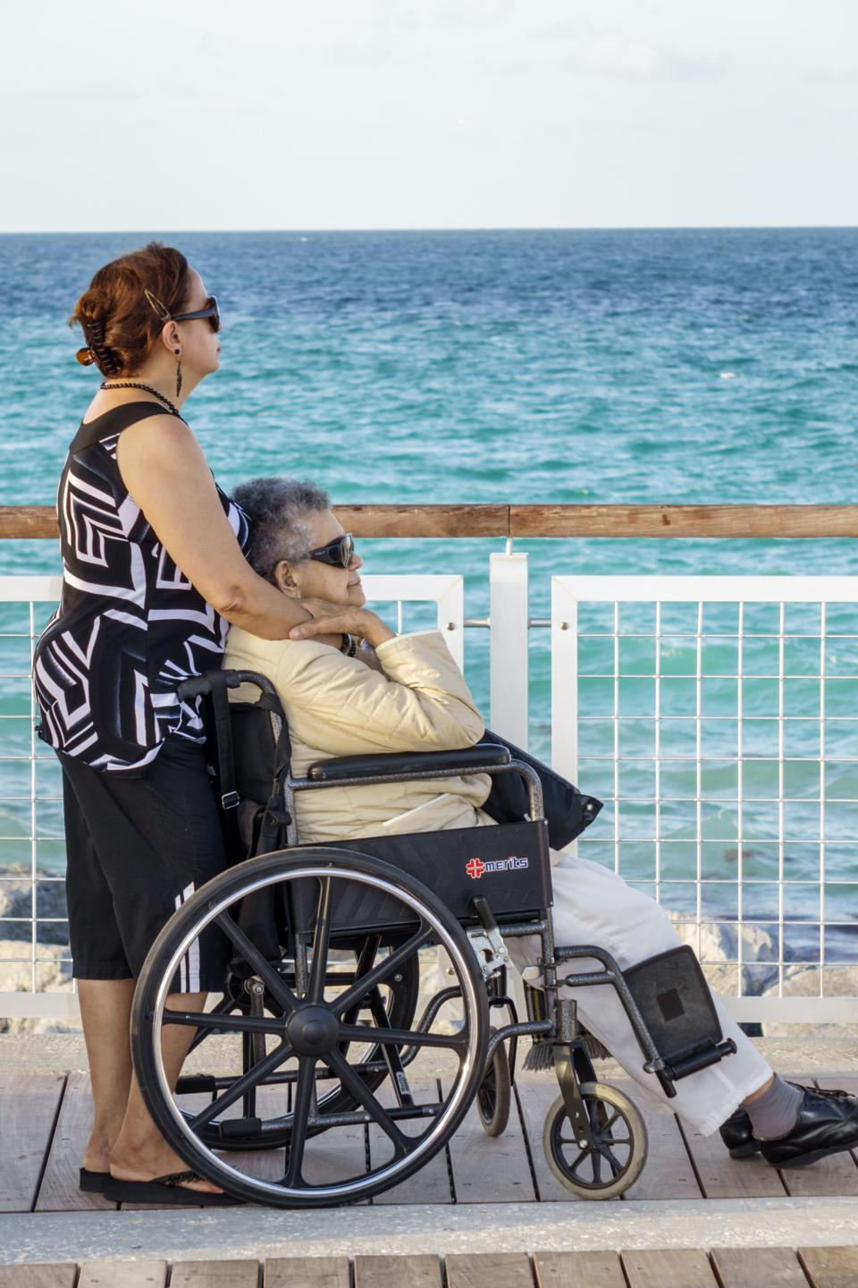 Senior disabled mother in a wheelchair with her daughter on South Pointe Park Pier.