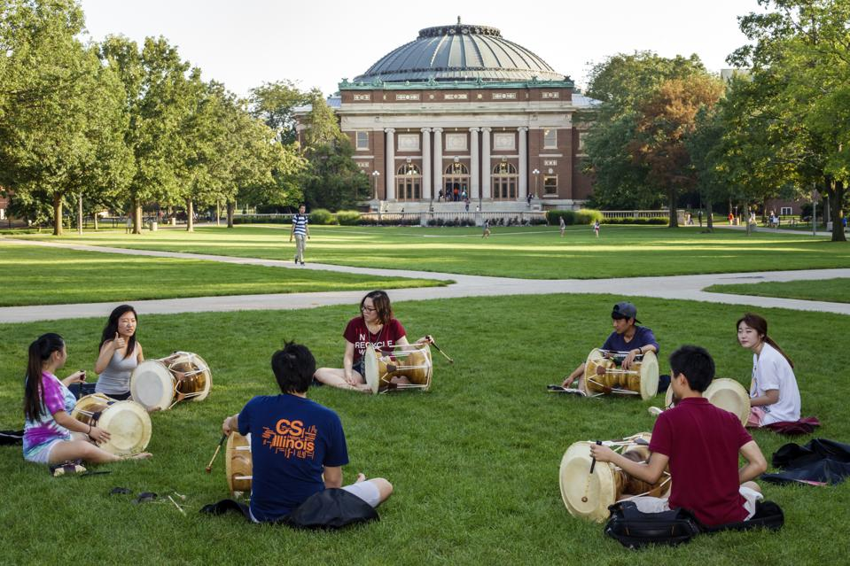 Teen students playing drums on campus of the University of Illinois.
