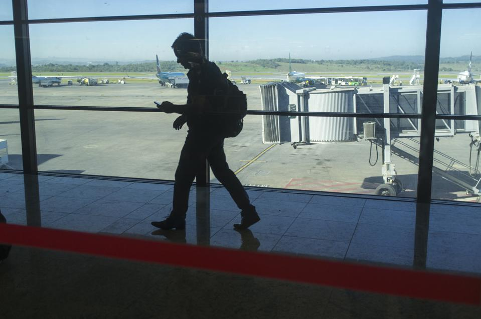 Passenger arrives at airport and immediately uses cell phone...