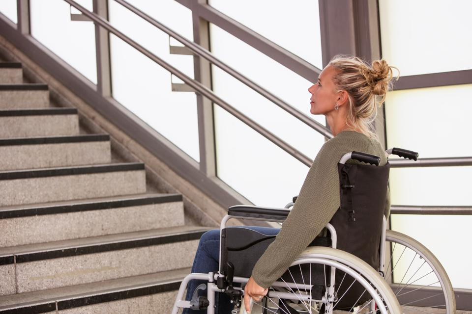 woman in a wheelchair in front of stairs
