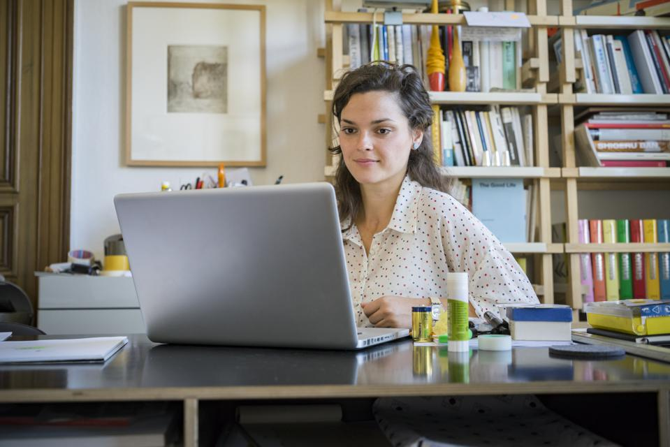 Young businesswoman using laptop at home
