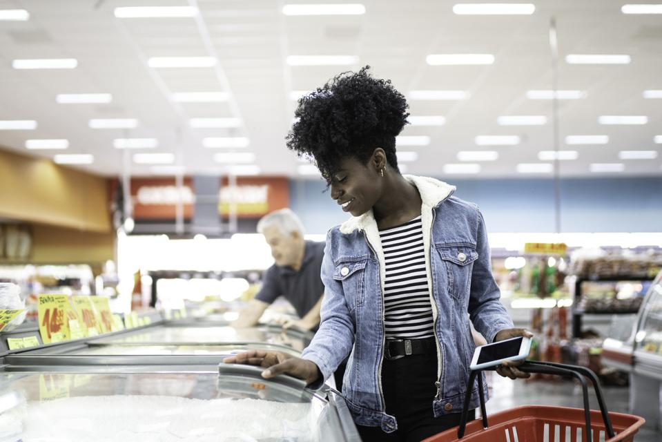 Young woman looking for products in the supermarket freezer