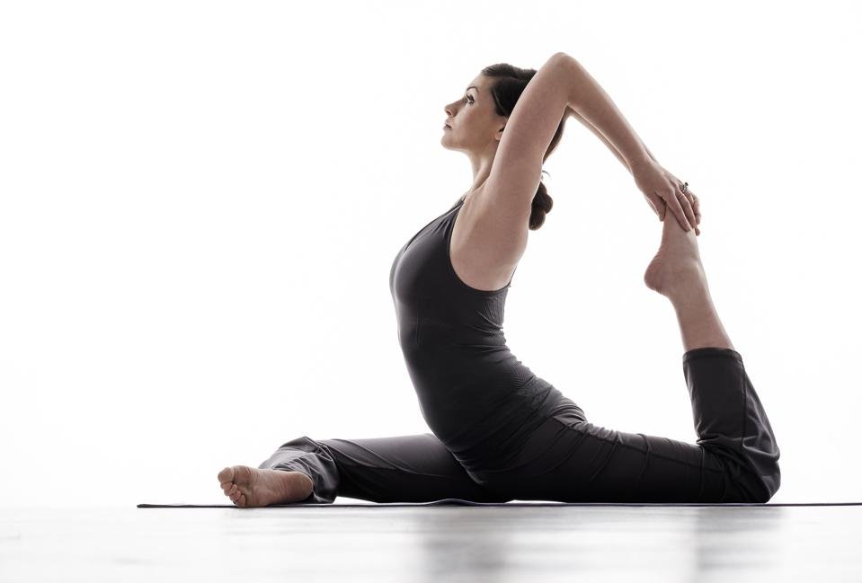 Side-view of young woman practicing yoga