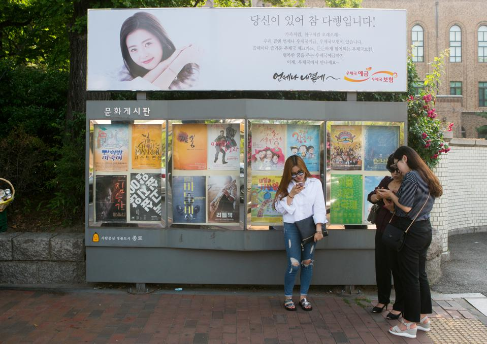 Women texting on their mobile phones in front of movie poster in the street, National capital area, Seoul, South korea