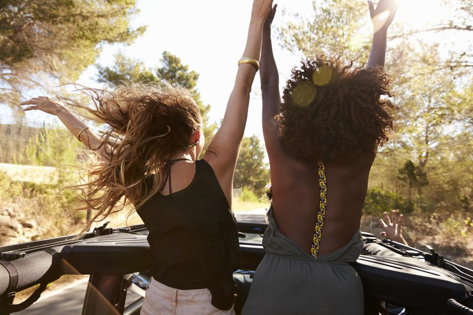 Two excited women stand in the back of open car, back