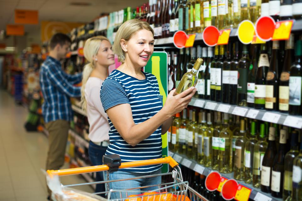 Woman buying wine in supermarket