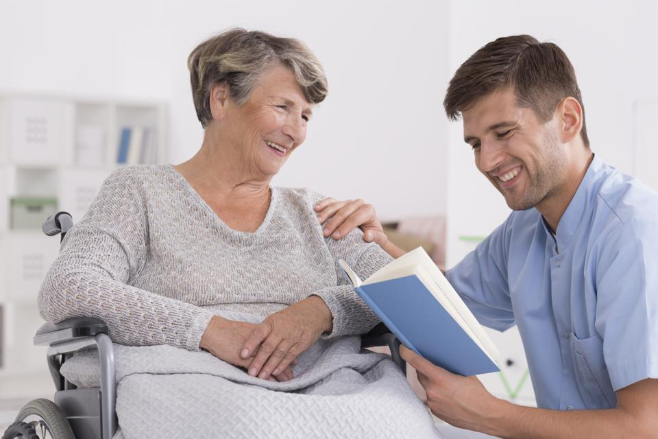 Adult son reading to his mother.