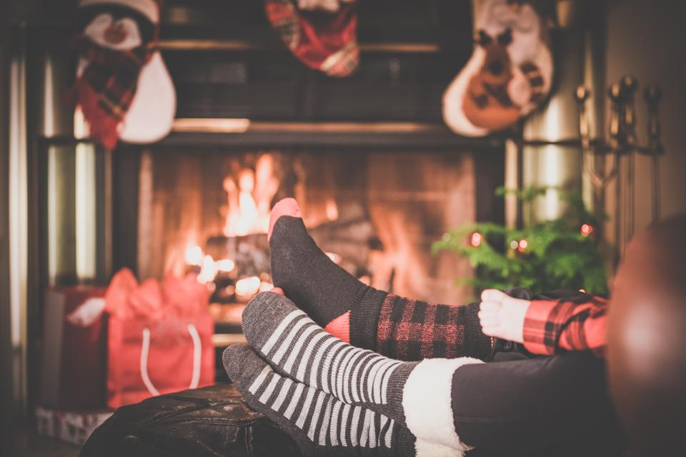 Two parents and baby feet Warming by Fireplace