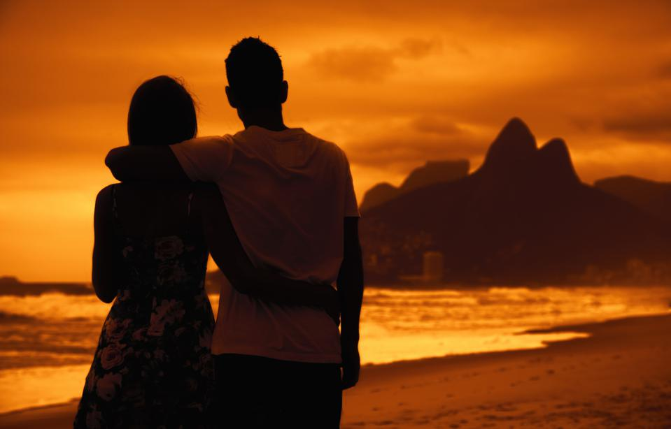 Love couple in arms on beach at sunset at Rio