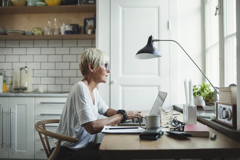 Side view of designer using laptop at home office