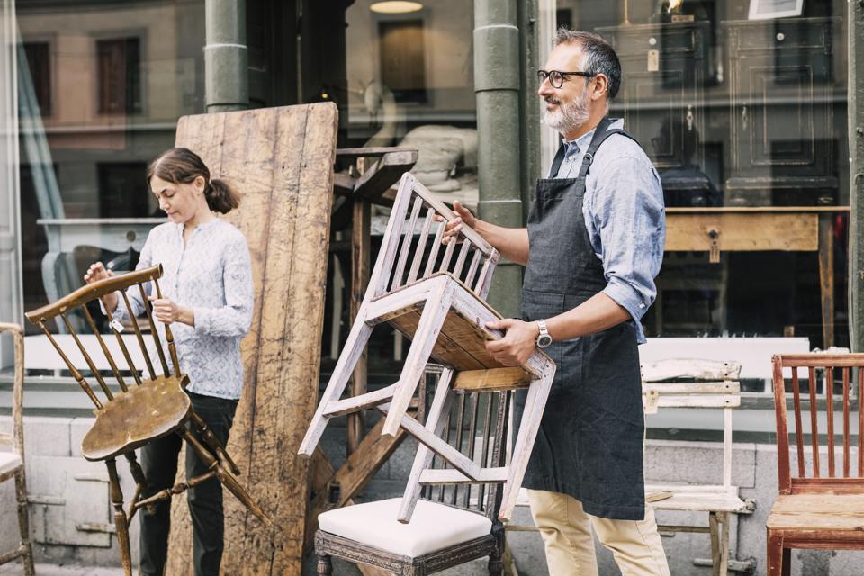 Business owners holding chairs while arranging outside store
