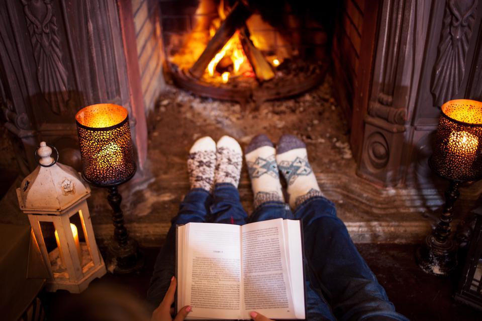 Couple relaxing at home reading a book. Feet in wool