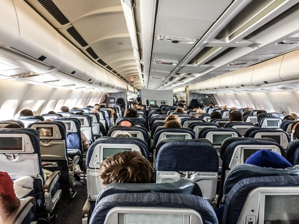 Passengers in a plane seen from behind above seats
