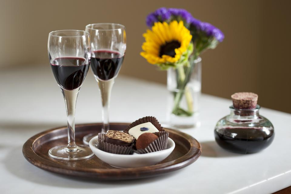 Dessert wine with chocolates on a wooden tray