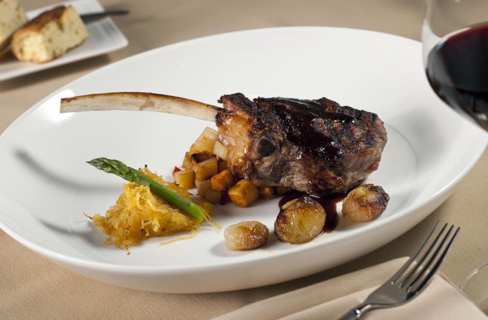 Bone in rib eye steak with red wine on white plate