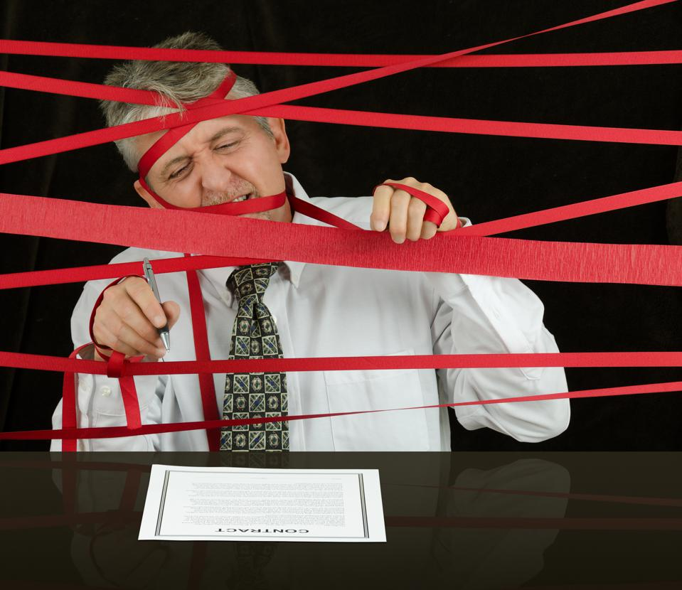 Frustrated business man caught in red tape stopping progress