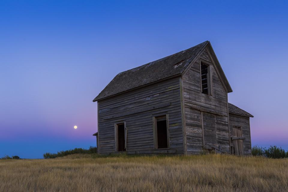 The Moon rising behind a rustic old farmhouse near Bow Island, Alberta. The Moon sits in the pink Belt of Venus with the blue shadow of the Earth below. (Photo by: Alan Dyer /VW PICS/Universal Images Group via Getty Images)