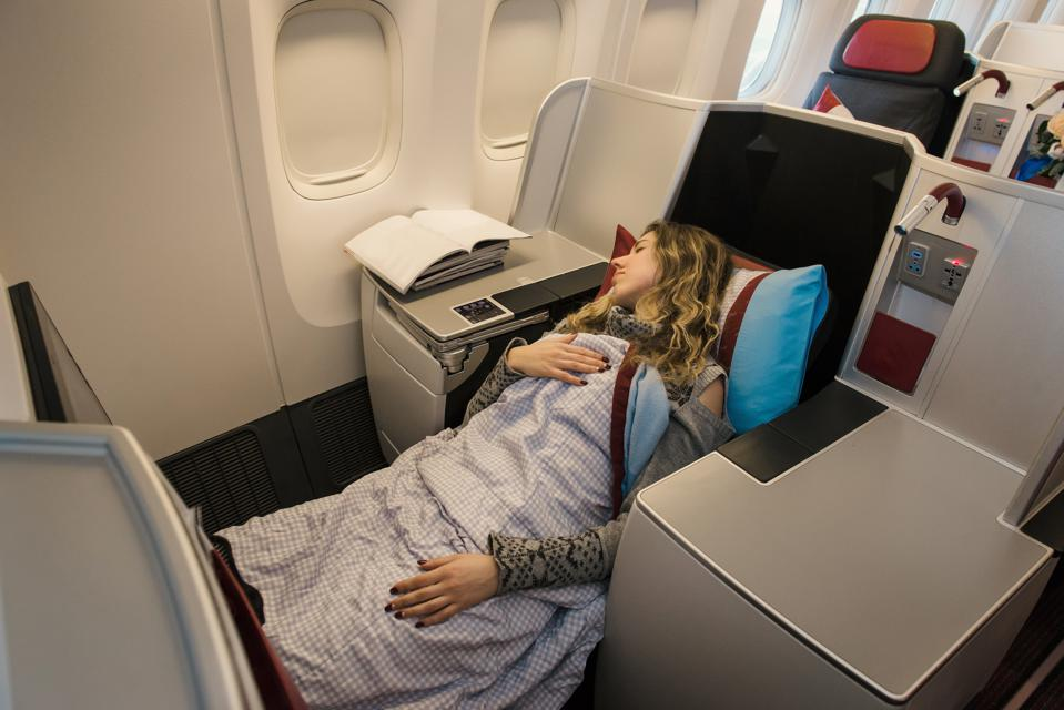 Woman passenger sleeping at the business class of airplane
