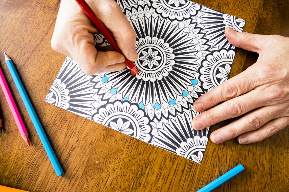 Woman Working On An Adult Coloring Book Design With Markers