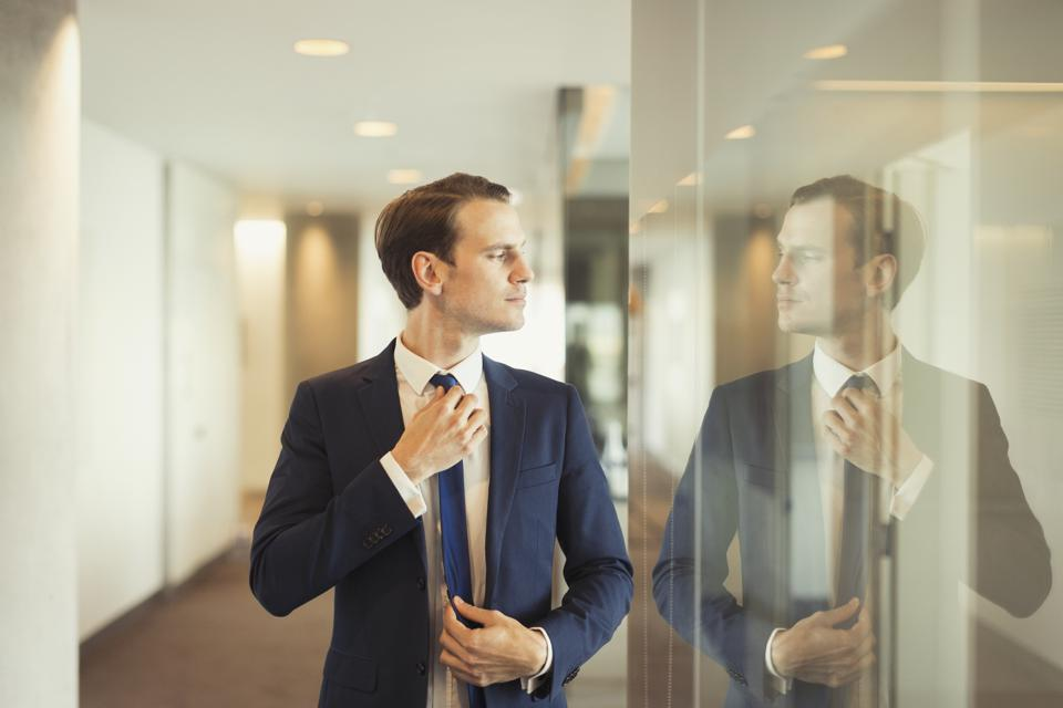 Confident businessman adjusting tie in office corridor