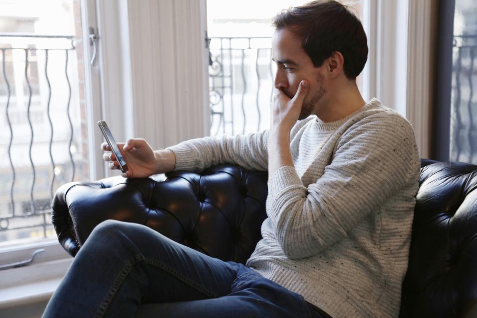 Mid adult man sitting on sofa, looking at smart phone