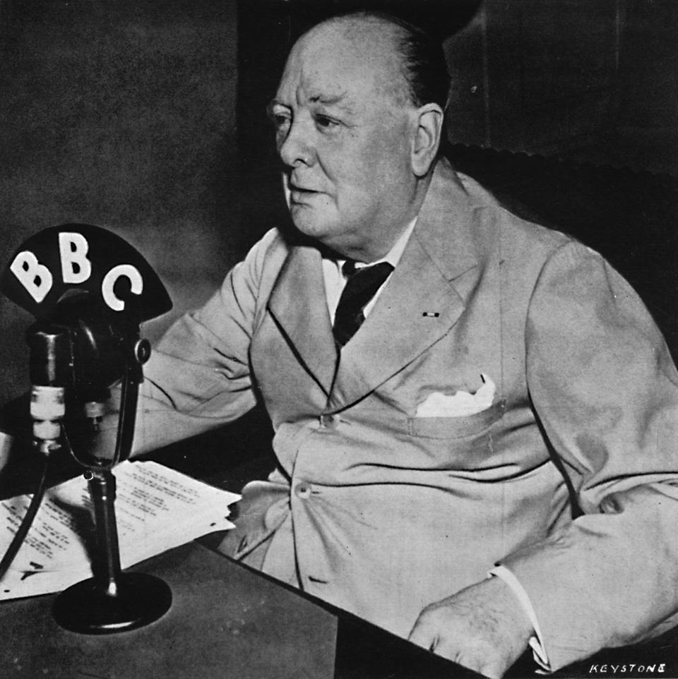Winston Churchill sitting in front of a BBC microphone