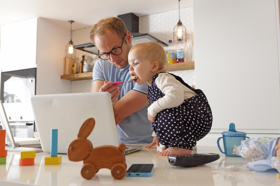 Father working on laptop whilst looking after toddler