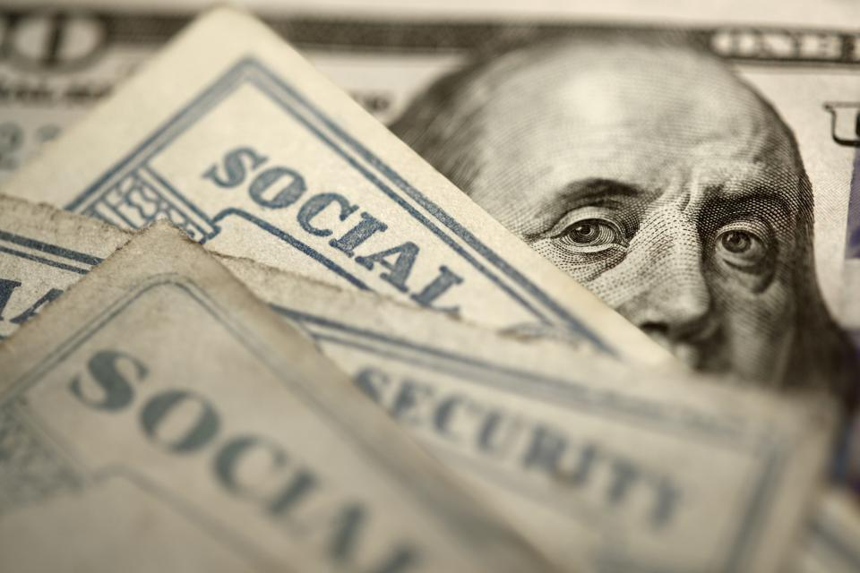 Social Security Cards On Top Of $100 Bill