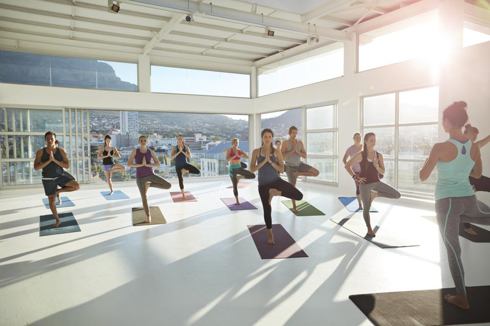 Large yoga class standing on one leg