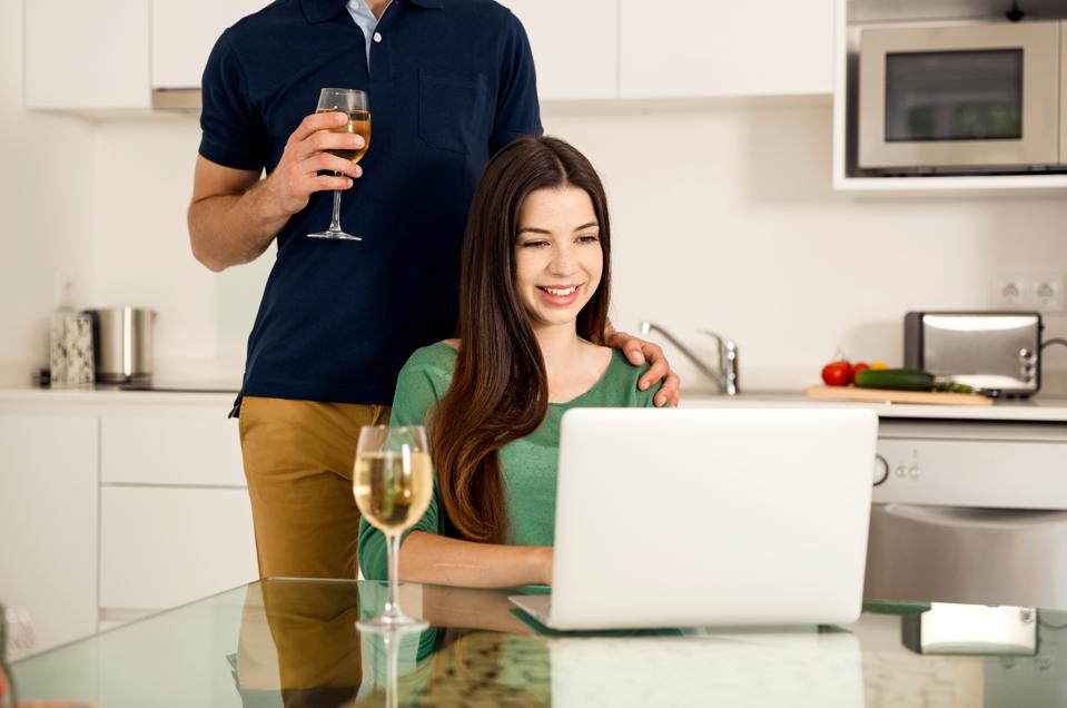 Couple drinking wine while taking online class