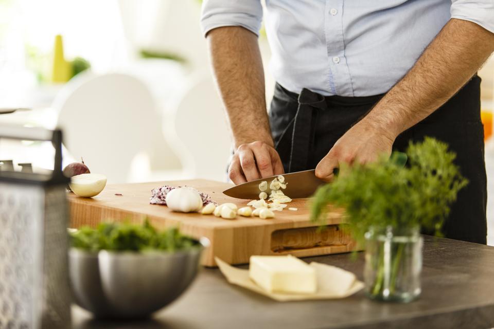 Chef slicing garlic on cutting board