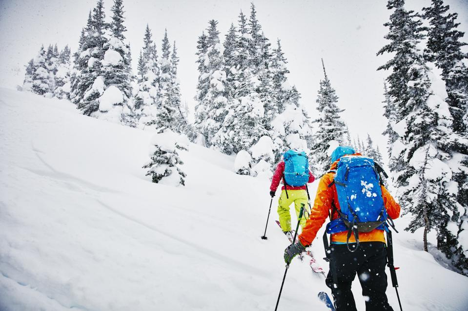 Two friends ascending mountainside on backcountry ski tour