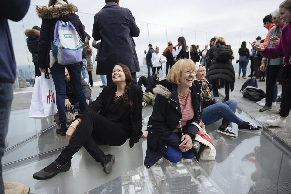 Tourists sit on the glass floor at Edge, the new observation deck on the 100th floor of 30 Hudson Yards in New York,