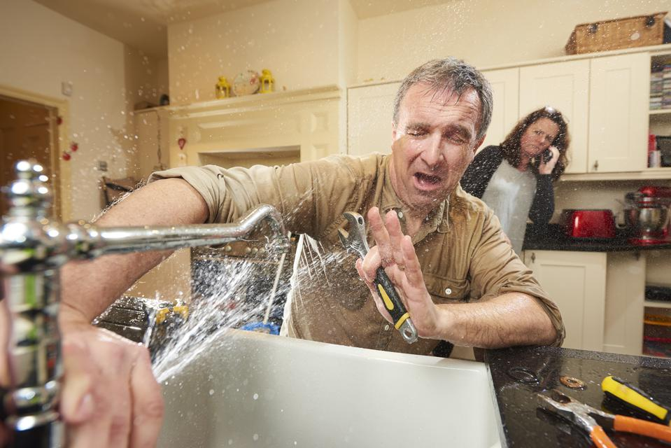 A do-it-yourselfer tries his hand at fixing the sink. His wife is already on the phone to an emergency plumber as water gushes from the broken tap.