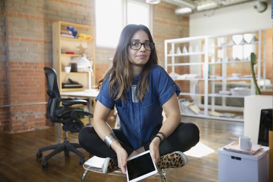 Portrait creative businesswoman cross-legged with digital tablet in office