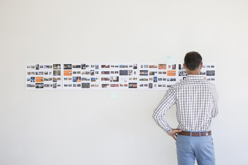 Businessman working in a creative design studio with images posted on a wall