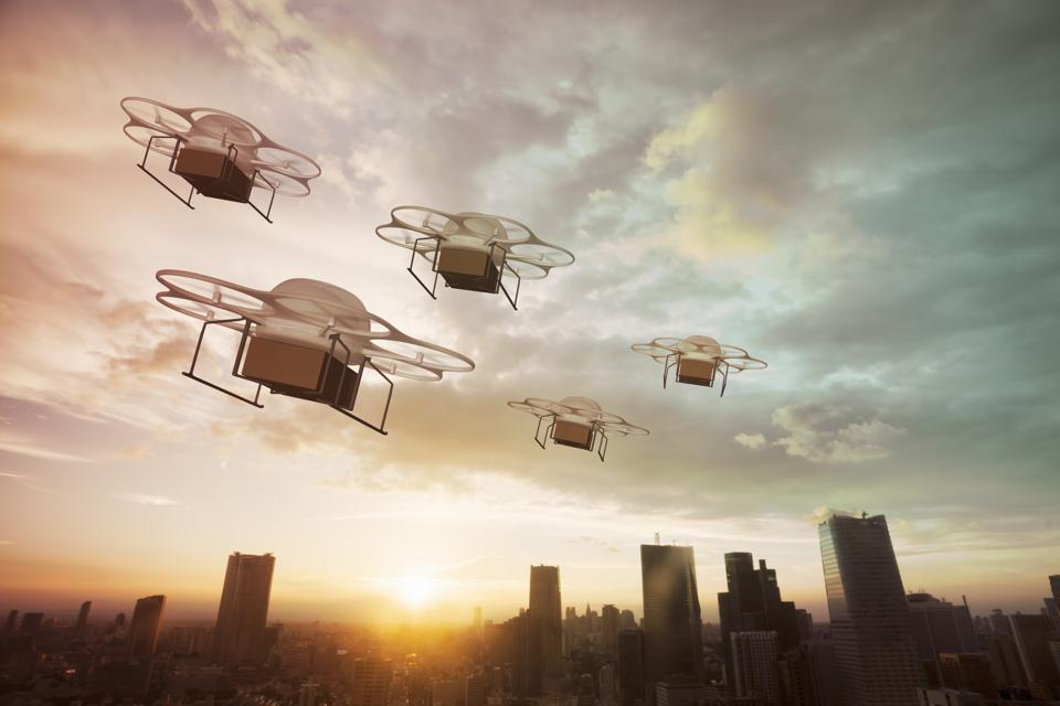 Five delivery drones flying above the city at sunset
