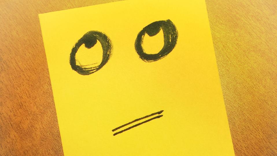 Hand drawn eye rolling emoji on yellow paper