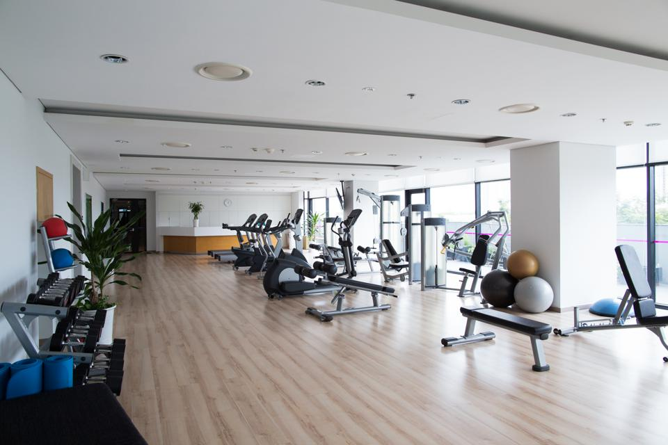 Big light gym with sports equipment in hotel