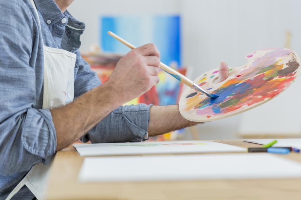 Artist blends paint on an artist's palette