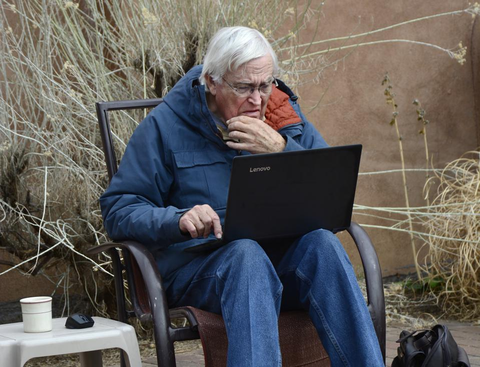 An elderly man looks at his laptop