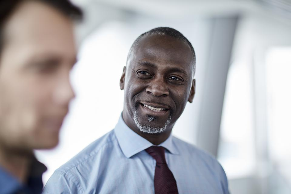 Smiling businessman listening to colleague