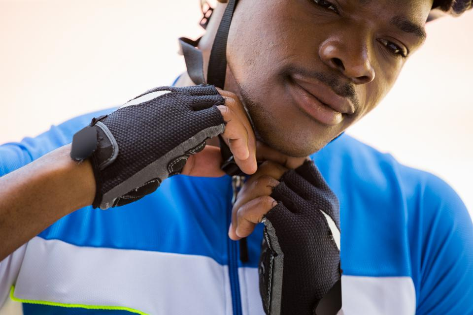 Close-up of an athlete putting on a cycling helmet