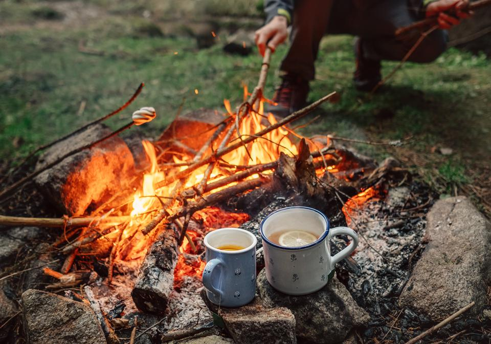 Two big mugs with hot tea and lemon near the campfire place