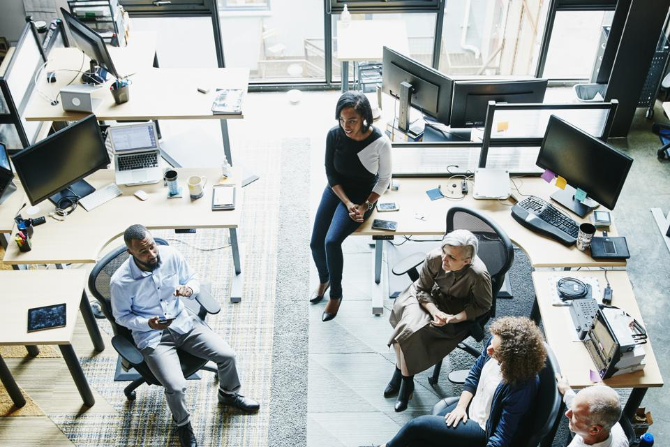 Businessman leading team meeting in high tech office overhead view