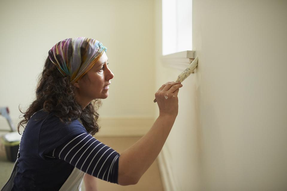 Female painter and decorator painting with brush