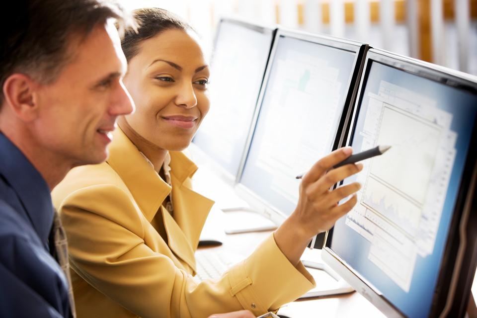 Smiling man and woman look pleased at stock market investing returns