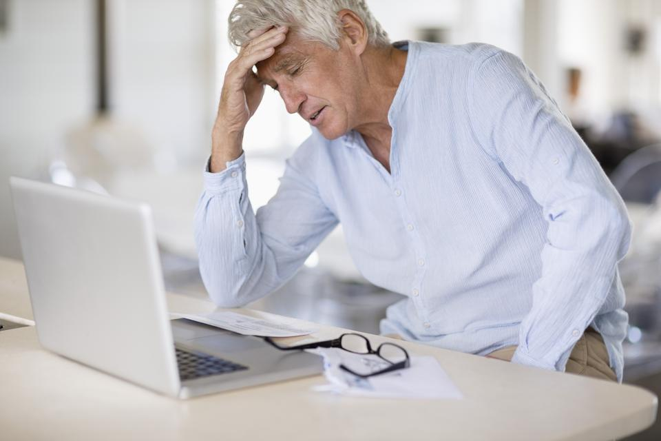 Worried senior man with bills and laptop on table